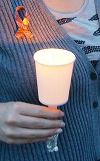 Carrying a lit candle and wearing a homemade red ribbon pin ath the Candle Parade
