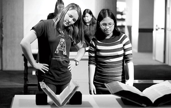 Kathryn Booth '15 (left) and Sabrina Oliveros '15 position a book at a student-curated exhibit at Thacher Gallery.