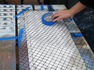 Close up of a student creating a mesh-reinforced thin-tile vault structure.