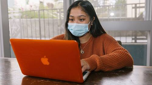 student wearing a mask and working on her laptop