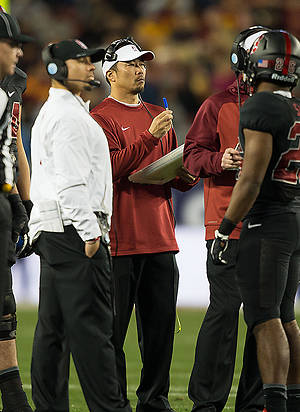Tsuyoshi Kawata on the field with Stanford football coaches and players