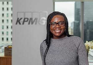 Princess Eyison '18 smiling in front of a wall with the KPMG logo