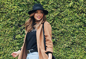 Maya wearing a black hat, black tee, light blue jeans, and tan jacket.