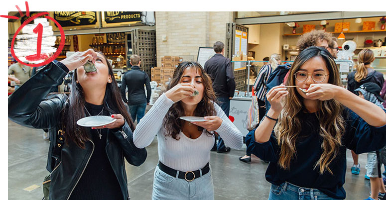 Three students eating raw oysters