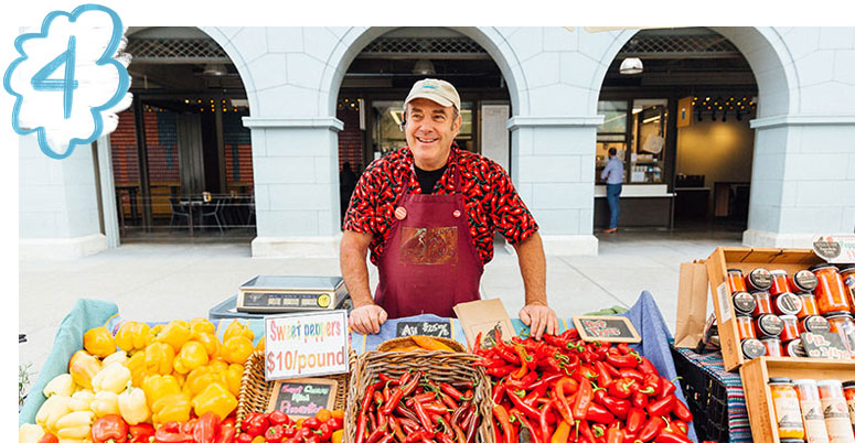 Person with peppers at farmers market booth